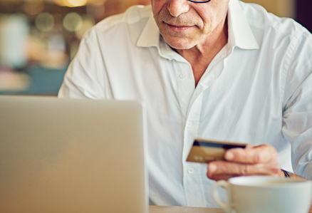 Mature man is shopping online using his laptop and credit card